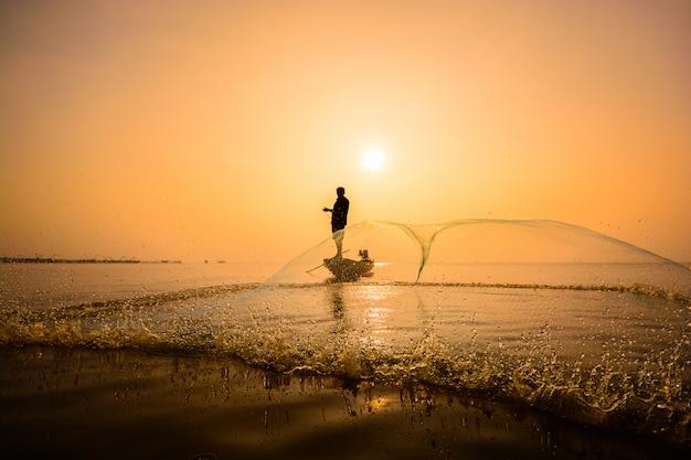 Pescador tirando red para pescar en la aldea pakpra, phatthalung, tailandia