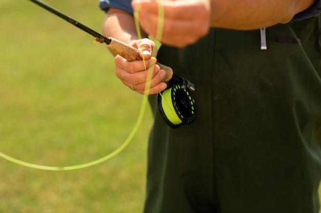 Pescador utilizando un carrete giratorio con una línea amarilla.