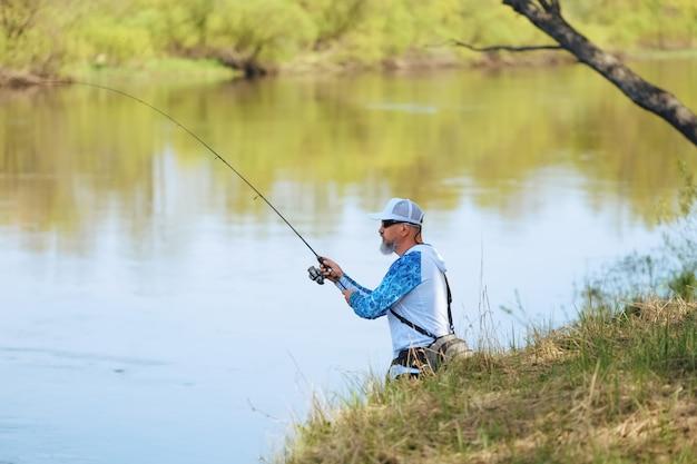 Pescador con una varilla giratoria captura de peces en un río