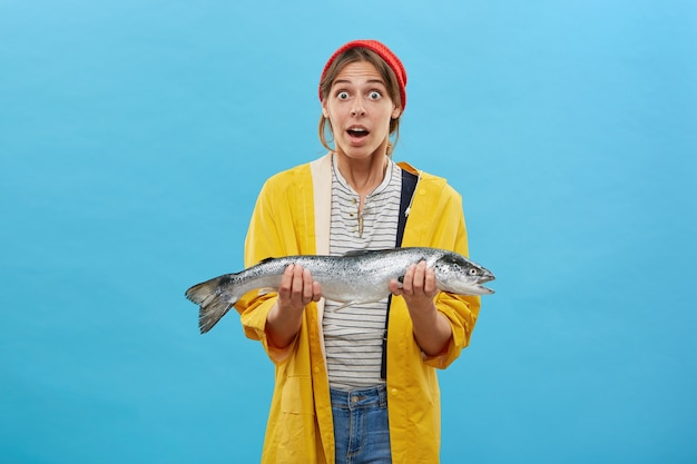 Pescadora asombrada vestida informalmente mientras sostiene un pez grande