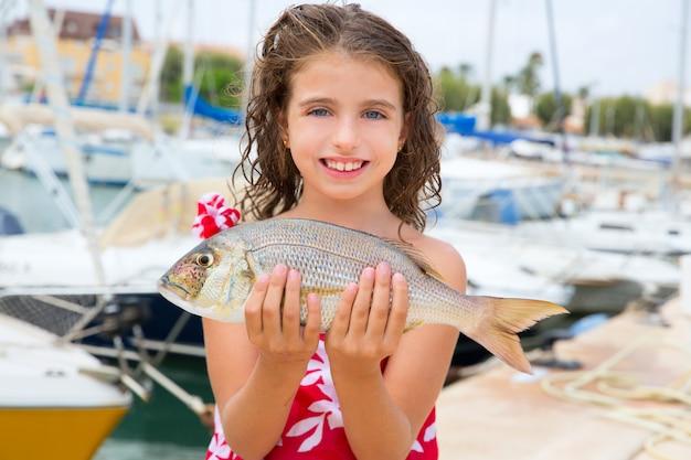 Pescadora niño feliz con la captura de peces dentex
