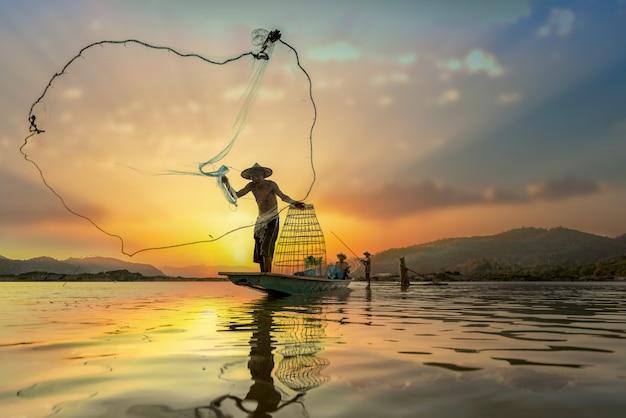 Pescadores asiáticos en barco de pesca en el lago
