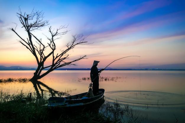 Pescadores caña de pescar con anzuelo sale a pescar temprano en la mañana con boa de madera