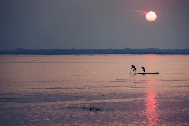 Los pescadores se ganan la vida usando trampas para atrapar peces que tienen redes como la captura de peces durante la puesta de sol.