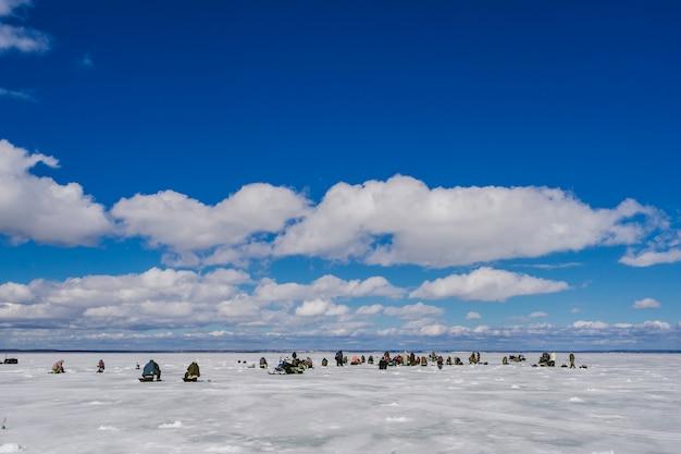 Los pescadores pescan en invierno en el hielo en un día