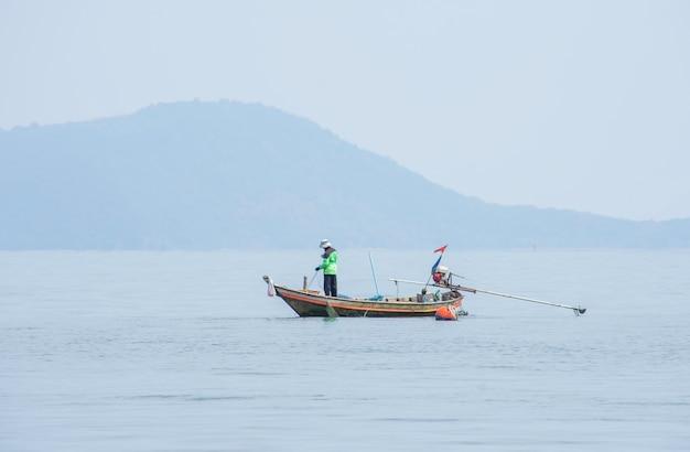 Pescadores que pescan redes en un barco en el mar en koh talu, prachuap khiri khan en tailandia.