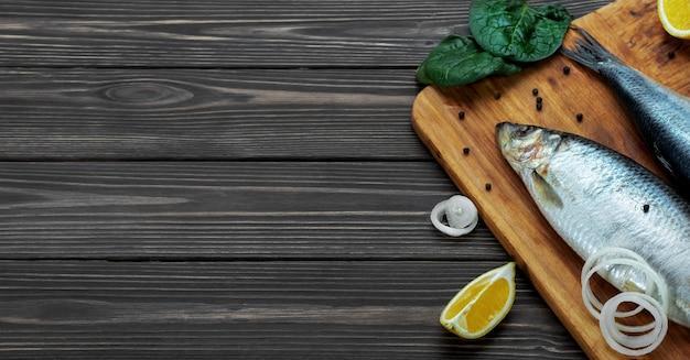 Pescados del arenque del atlántico en escabeche sobre una tabla para cortar junto a especias y limón