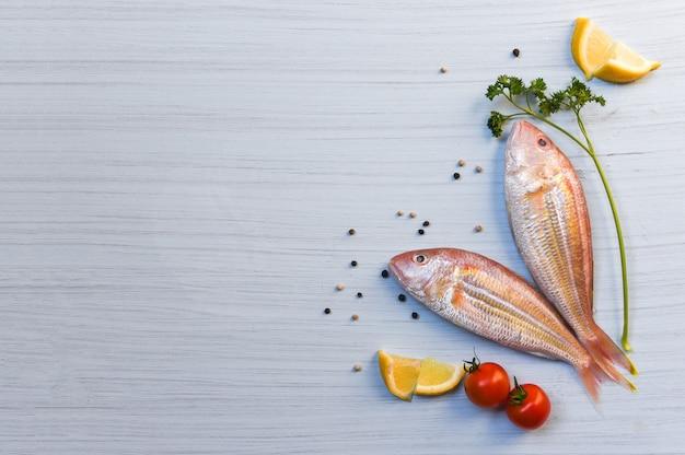 Pescados y mariscos frescos de los pescados crudos con las hierbas y las especias con la semilla de la pimienta del tomate del perejil del limón en el fondo de madera blanco