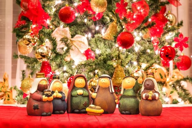 Pesebre navideño delante del árbol de navidad