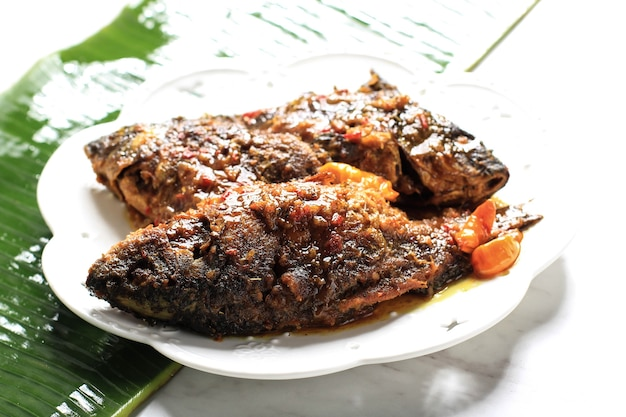 Pesmol pescado con goldfish. agregue pescado frito a la sartén. pesmol receta típica de pescado de java occidental, indonesia, con sabor agridulce y picante