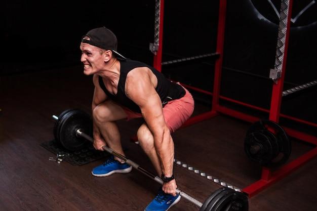 Peso muerto sports man lifting barbell row en el gimnasio