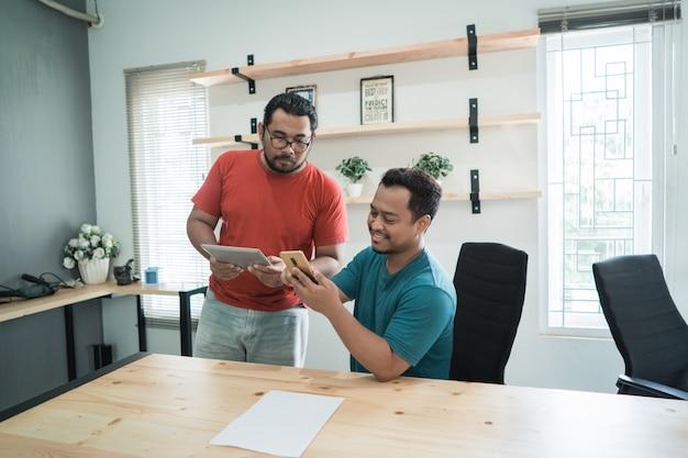 La pestaña de uso y reunión de dos trabajadores y el teléfono inteligente discuten sobre los programas de la compañía