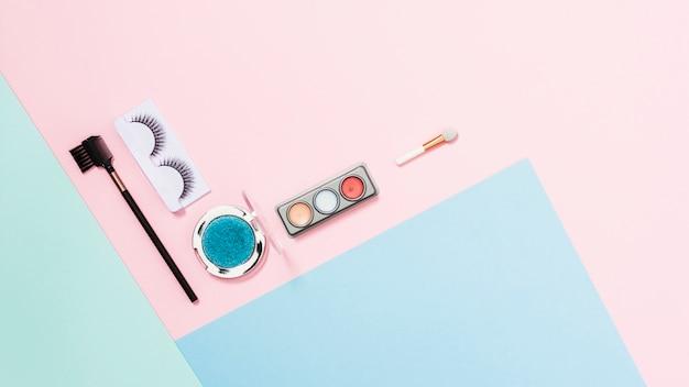 Pestañas artificiales; paleta de sombra de ojos y pincel de maquillaje en el fondo de color triple
