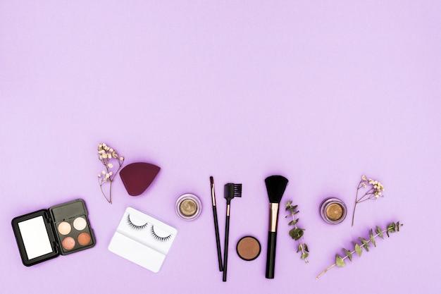 Pestañas artificiales; paleta de sombras de ojos; licuadora; polvos compactos y pinceles de maquillaje con ramita y gypsophila sobre fondo morado
