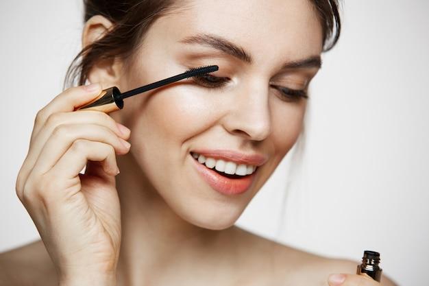 Pestañas hermosas lindas del tinte de la muchacha que sonríen sobre el fondo blanco. concepto de belleza salud y cosmetología.