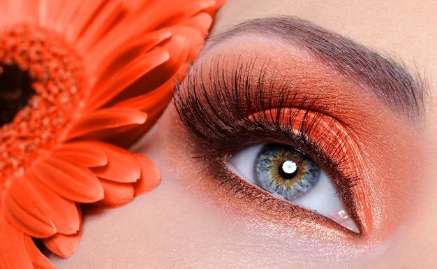 Pestañas postizas y maquillaje de ojos de moda con flor de naranja