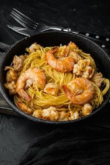 Pesto de espagueti de mariscos listo para comer, en una sartén de hierro fundido, sobre la mesa de piedra negra