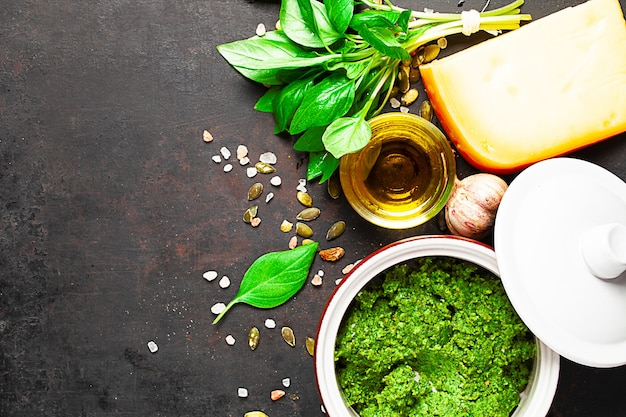 Pesto en tarro de cerámica e ingredientes con textura