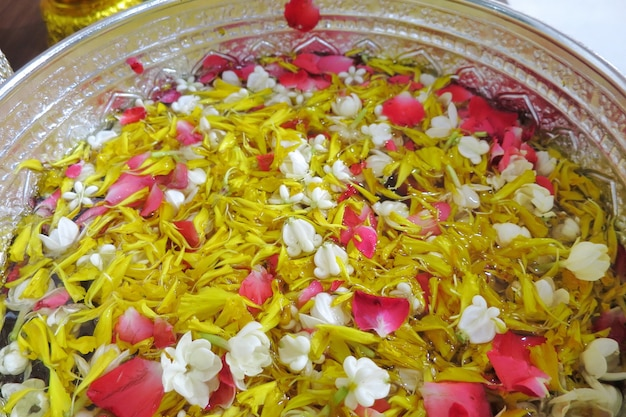 Pétalo de rosas, caléndula y jazmín en un recipiente de plata sobre tela de algodón azul, festival songkran en tailandia.