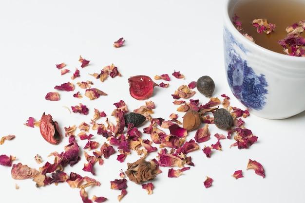 Pétalos color de rosa secados y taza de té aislados en el fondo blanco