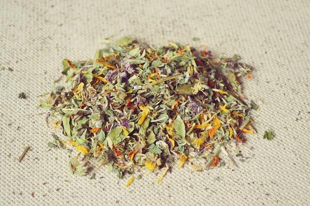 Pétalos de flores y flores secas se encuentran en la tela de arpillera, filtro de primer plano