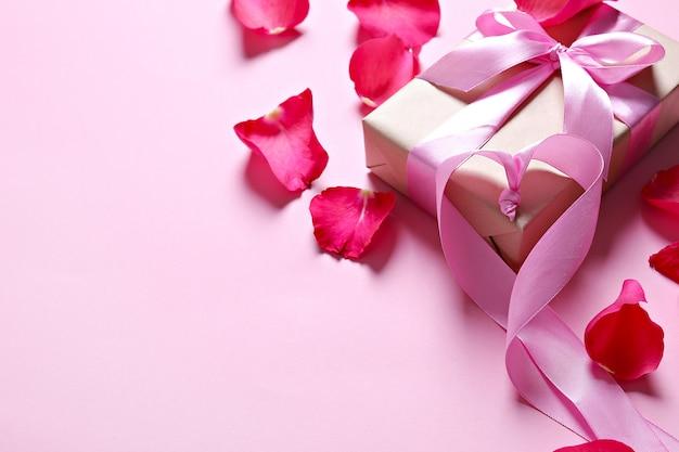 Pétalos de rosa y caja de regalo con lazo rosa