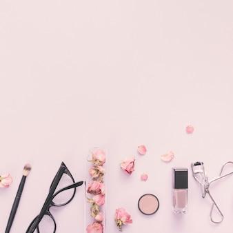 Pétalos de rosa con cosméticos en mesa.