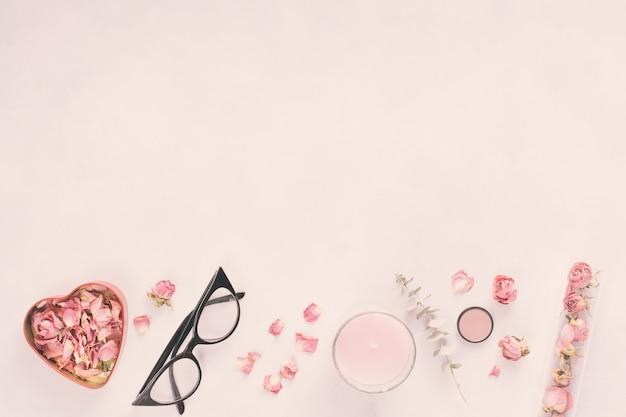Pétalos de rosa con gafas y vela en mesa.