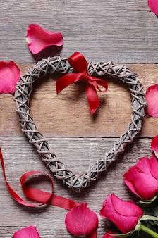 Pétalos de rosa con marco en forma de corazón