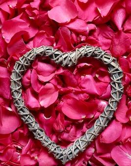 Pétalos de rosa y marco en forma de corazón Foto gratis