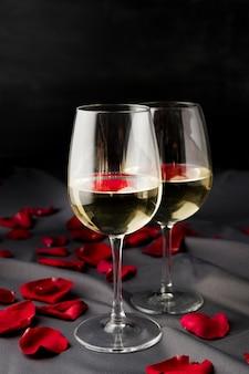 Pétalos de rosa de san valentín con copas de vino.