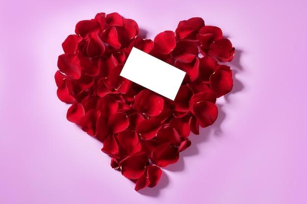 Pétalos de rosas rojas en forma de corazón, copia espacio nota en blanco