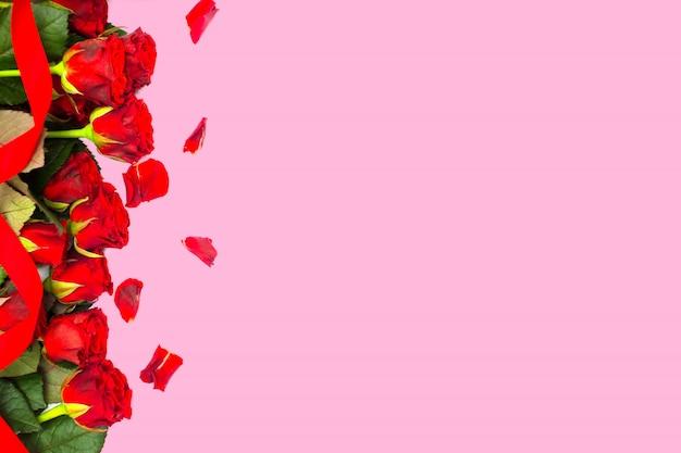 Pétalos de rosas rojas sobre rosa