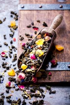 Pétalos de rosas secas en una cuchara de madera