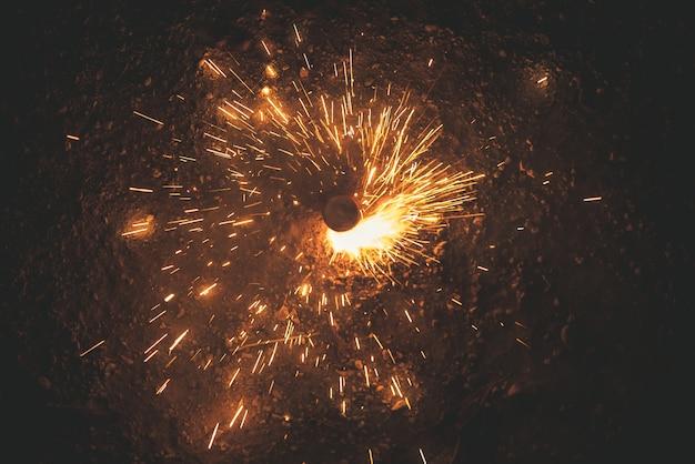 Petardos que giran iluminando la noche con sus chispas.