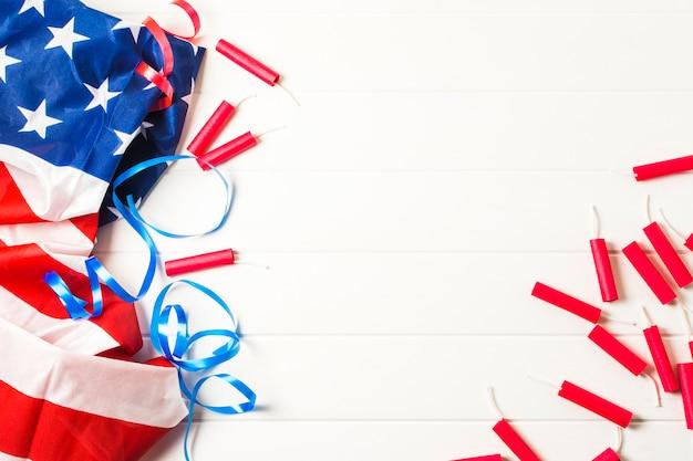 Petardos rojos y cintas azules con la bandera estadounidense de estados unidos en mesa blanca