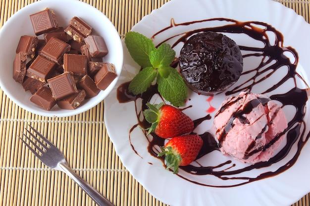 Petit gateau con helado en plato blanco con fresa sobre mesa de madera rústica
