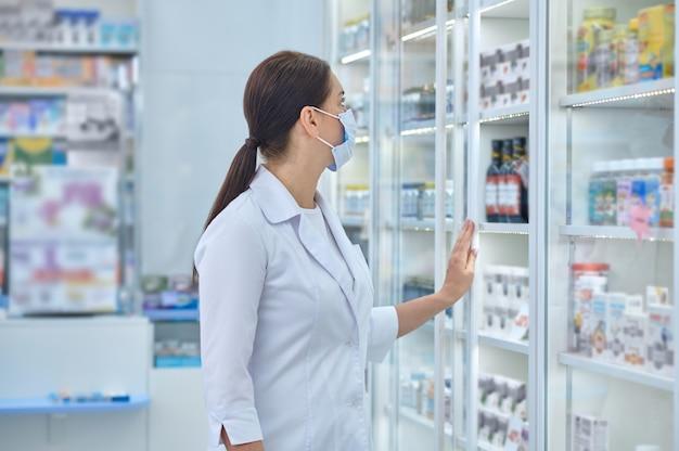Pharmaceutist experimentado examinar suplementos dietéticos en los estantes de las farmacias