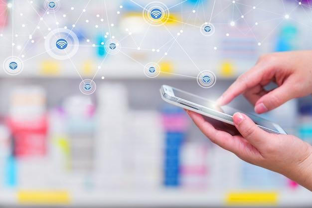 Pharmacistusing teléfono inteligente móvil para la barra de búsqueda en la pantalla de la farmacia farmacia