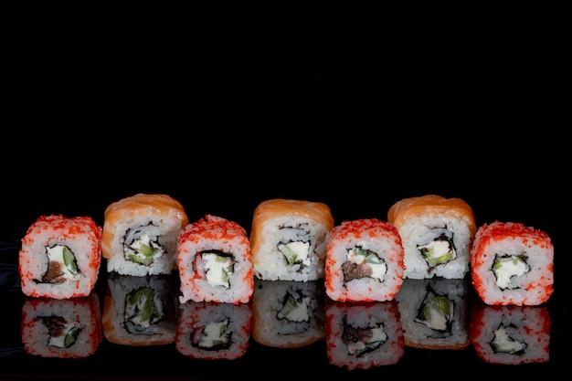 Philadelphia roll con salmón, queso y pepino en negro con reflejo