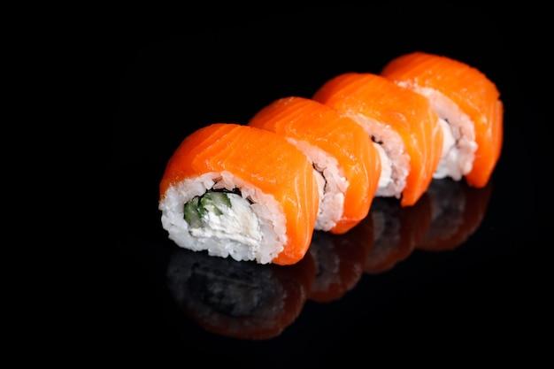 Philadelphia sushi roll sobre un fondo negro con reflejo.