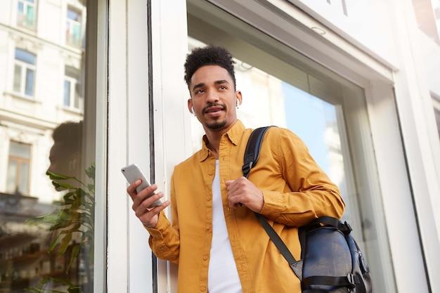 Phortrait de joven alegre afroamericano con camisa amarilla, caminando por la calle y sostiene el teléfono, charlando con amigos, escuchando su canción favorita en auriculares, se ve genial.
