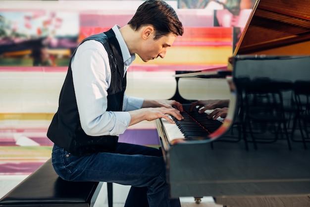 Pianista masculino practicando composición en piano de cola