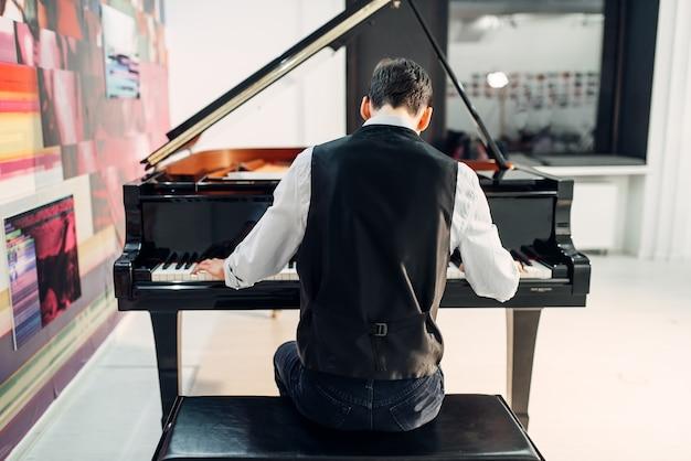 Pianista masculino tocando la composición en el piano de cola