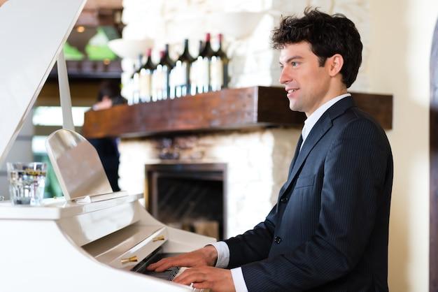 Pianista en un piano crea una hermosa atmósfera musical en un restaurante de alta cocina