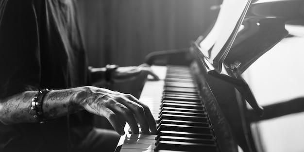 Pianista practicando en un piano de cola con música clásica.