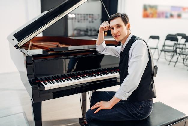 Pianista profesional en el piano de cola negro
