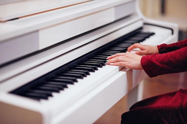 Pianista tocando en un piano blanco. las manos de cerca.