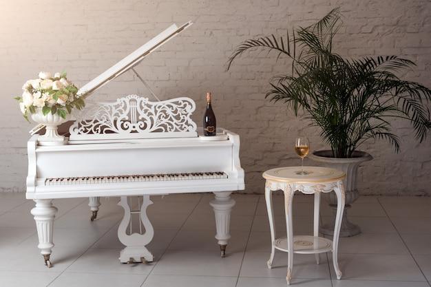 Piano de cola en un interior clásico de lujo blanco con vino, palmeras y flores.