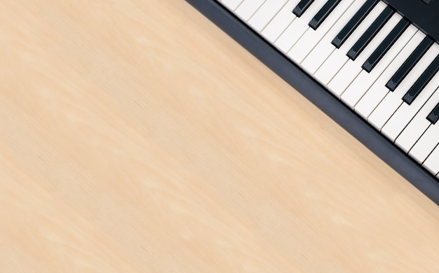 Piano teclado midi sobre fondo de mesa de madera con espacio de copia, equipo de entretenimiento creativo para el estudio en el hogar, tecla de sintetizador